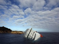File photo of the Costa Concordia cruise ship on its side, half-submerged and threatening to slide into deeper waters