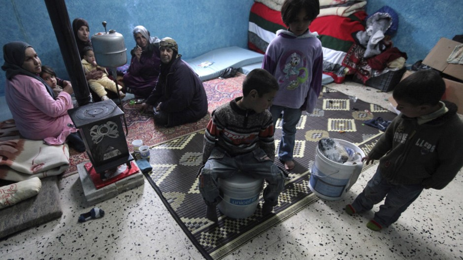 Syrian refugees who fled the violence in Syria are seen their temporary home in a school at Wadi Khaled area in northern Lebanon