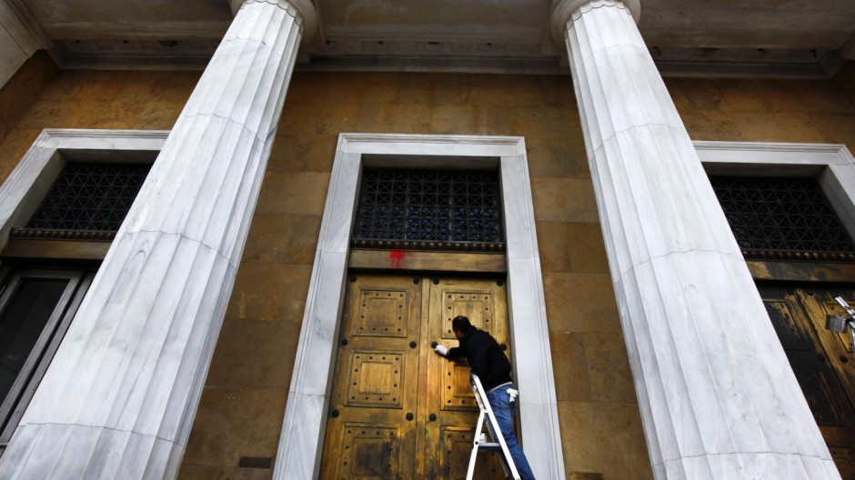 A worker cleans paint thrown by anti-austerity protesters at the facade of the Bank of Greece in central Athens