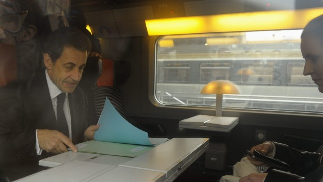 France's President Sarkozy sits in a TGV train before his departure for Lille