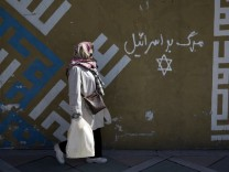 Woman walks past writing on a wall in Persian script that reads, 'Down with Israel', in northern Tehran