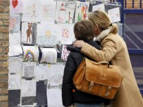 A woman and child look at condoleance notes and drawings posted on a wall outside the Sint Lambertus school in Belgium after deadly school trip bus crash in Switzerland