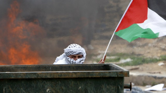 A Palestinian protester takes cover during clashes with Israeli troops near Ramallah