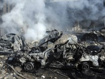 A handout photo distributed by Syrian News Agency (SANA) shows destroyed vehicles after explosions near the intelligence centre  in Damascus