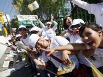 The faithful gesture as they wait for Pope Benedict XVI during his visit to Mexico