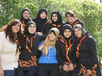 British Muslim girl scouts pose with their newly designed uniform, which includes a 'hoodie dress' to stop headscarves falling off and long sleeves