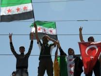 Syrische Flüchtlinge schwenken die Revolutionsflagge und die türkische Fahne