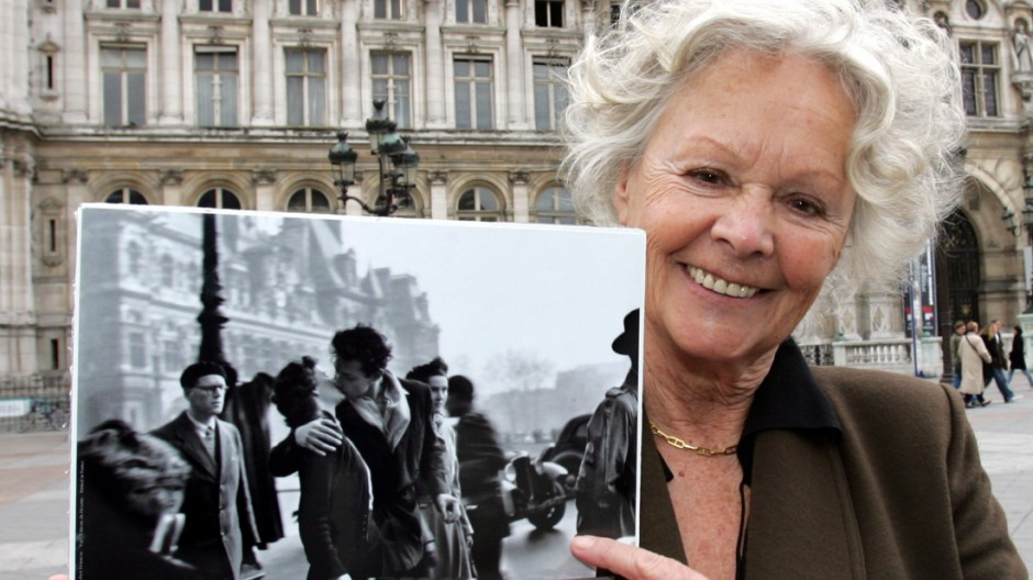 Francoise Bornet, former French actress who claims she and her boyfriend are subjects of famous 'The Kiss at City Hall' photography by Robert Doisneau, holds reproduction of photo in Paris