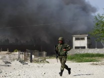 A Afghan National Army soldier runs near the Provincial Reconstruction Team (PRT) as smoke rises from the site of an attack in Jalalabad
