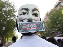 A protester, wearing a Guy Fawkes mask with a dollar note, take part in a demonstration to protest cuts in health reforms in Madrid