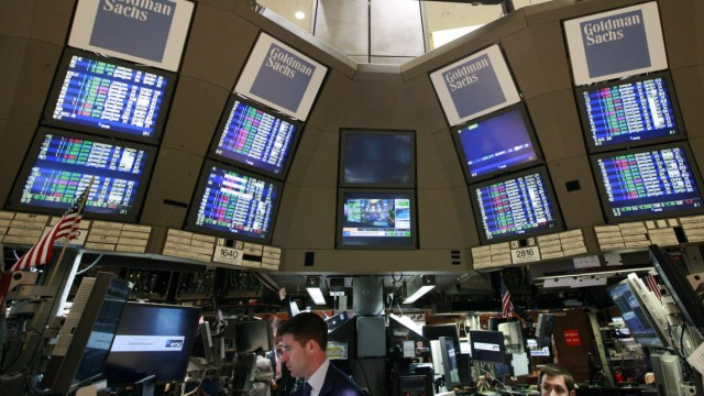 Traders work at the Goldman Sachs kiosk on the floor of the New York Stock Exchange