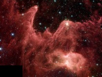 This image shows an infrared data taken by NASA's Spitzer Space Telescope of a region dubbed the 'Mountains of Creation.' Towering pillars of dust are aglow with the light of embryonic stars (white/yellow). The added detail in the Spitzer image reveals a