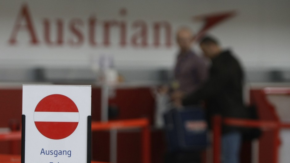 The logo of Austrian airline is seen behind an exit sign at a check-in desk at Vienna International Airport