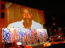 Passersby walk under a projection that is part of the non-profit organization Invisible Children's 'Kony 2012' viral video campaign, in New York
