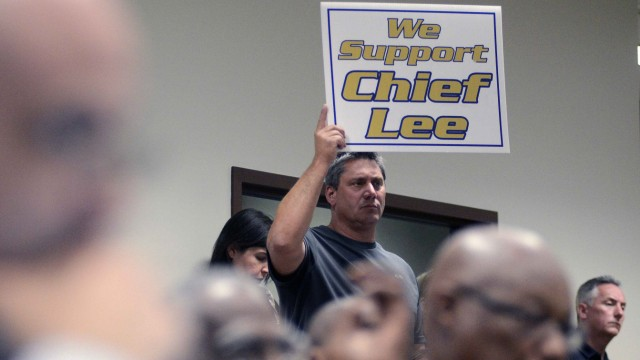 Korolowski holds up a sign in support of embattled Sanford Police Chief Lee during a special meeting by the Sanford City Commission in Sanford
