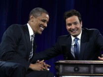 U.S. President Barack Obama smiles next to Jimmy Fallon at an interview during a televised taping of the 'Late Night with Jimmy Fallon' show at the University of North Carolina