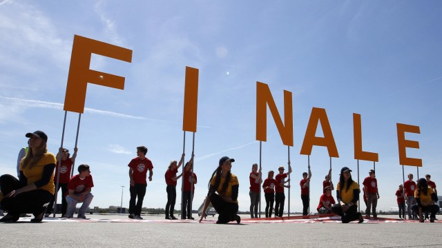 People hold up letters that read 'Final' before the arrival of the Bayern Munich soccer team at Munich's airport