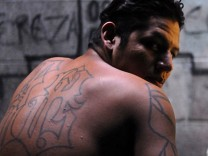 An gang member and inmate sits inside the jail in Quetzaltepeque