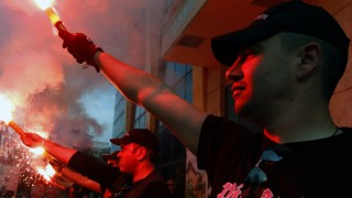 Members of the Greek extreme right Golden Dawn party hold red flares outside the town hall of Perama town
