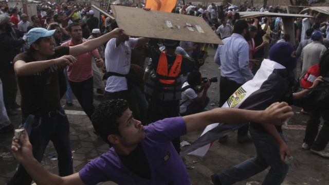Protesters throw stones at army soldiers during clashes at Abbasiya square near Egypt's Defence Ministry in Cairo
