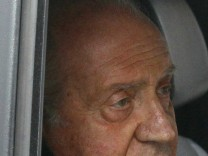 Spain's King Juan Carlos looks on from inside a car as he leaves a hospital after being discharged in Madrid