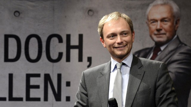 Christian Lindner is pictured in front of an election poster showing Wolfgang Kubicki during an election rally in Kiel