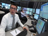 A trader reacts at his desk in front of the DAX board at the Frankfurt stock exchange