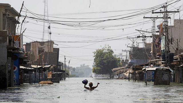 A man displaced by flooding wades down a flooded street as he returns to his town of Khairpur Nathan Shah