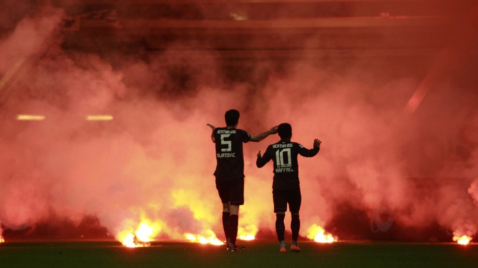 Hertha Berlin players react to flares thrown by their supporters onto the field during their German Bundesliga first division relegation soccer match against Fortuna Duesseldorf in Duesseldorf