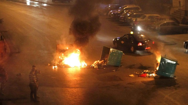 Garbage bins set on fire by Lebanese Sunni Muslim residents are seen blocking a road in Beirut