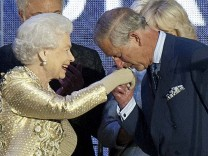 Britain's Prince Charles kisses the hand of his mother Queen Elizabeth at the end of her Diamond Jubilee concert in front of Buckingham Palace in London