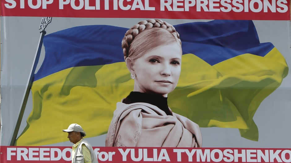 A man walks past a board with a portrait of jailed former Ukrainian Prime Minister and opposition leader Yulia Tymoshenko in central Kiev