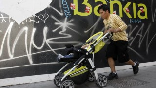 A man pushes a pram in front of a Bankia bank logo in Madrid