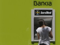 Woman uses a Bankia bank ATM in Madrid