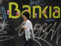 A woman walks past a defaced logo of nationalized lender Bankia in Madrid