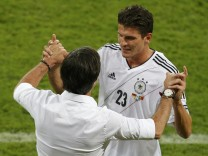 Germany's Gomez celebrates with coach Loew after scoring against Portugal during their Group B Euro 2012 soccer match at the new stadium in Lviv