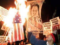 ARGENTINE DEMONSTRATORS BURN A US FLAG OUTSIDE GOVERNMENT HOUSE DURING 24-HOUR STRIKE