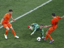 Denmark's Andersen is challenged by Netherlands' Huntelaar and van Persie during their Group B Euro 2012 soccer match at the Metalist stadium in Kharkiv