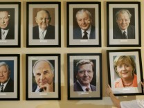 Restaurant manager places a portrait  of new German Chancellor Merkel on a wall at the restaurant 'Kanzlereck' in Berlin