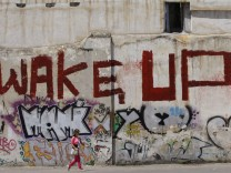 Woman walks past a wall covered with a graffiti in Athens