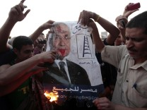 Protesters burn a defaced poster of presidential candidate Shafik at Tahrir square in Cairo