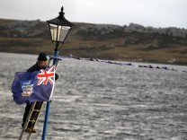 A man hangs a Falklands flag in Stanley, during commemorations for the 30th anniversary of the Falklands War