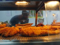 A customer looks at the battered fish at the Quality Fish Bar in north London