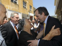 Leader of conservative New Democracy party Samaras is greeted by a woman during a visit on the island of Rhodes
