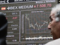 A trader looks at electronic boards at the Madrid stock exchange