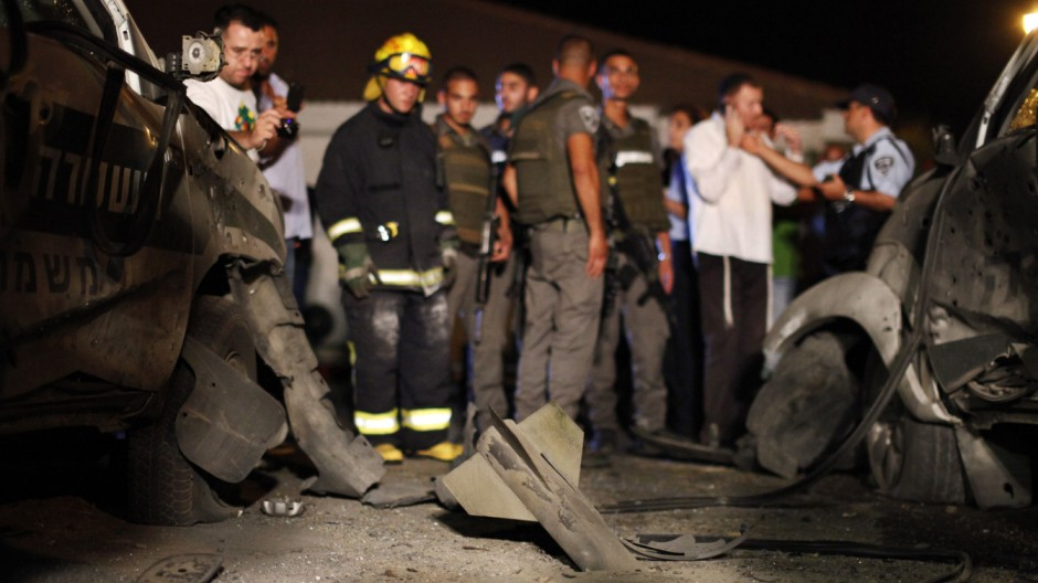 Israeli security forces stand at the scene where a rocket fired from Gaza exploded inside a border police base in south Israel