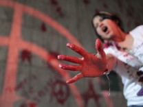 A protester shows her hand with red paint during a demonstration where they threw red paint on the wall of the building belonging to Brazil's Vale SA mining company, in Rio de Janeiro