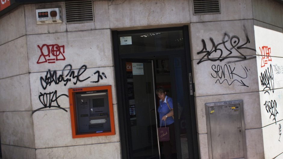 A woman walks out of a Catalunya Caixa savings bank branch in Madrid