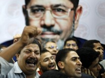 Supporters of the Muslim Brotherhood's presidential candidate Mohamed Morsy celebrate in front of his picture at his headquarters in Cairo