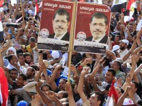 Supporters of Muslim Brotherhood's presidential candidate Mohamed Morsy celebrate his victory at the election at Tahrir Square in Cairo